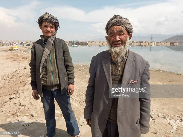 Garbage collector and his young aide posing near a lake in Kabul