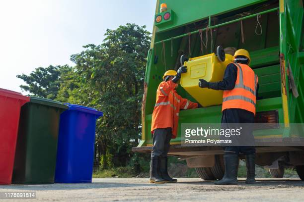 [garbage collector] asian worker of urban municipal recycling garbage collector truck loading waste and trash bin in thailand, trash keeper. - politics stock pictures, royalty-free photos & images