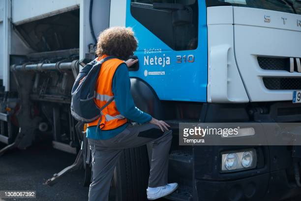 a garbage collector entering a trash truck. - entering stock pictures, royalty-free photos & images