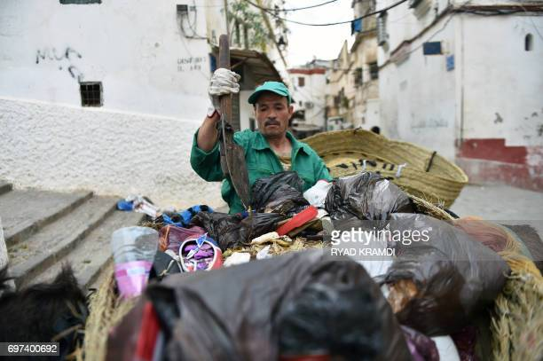 A garbage collector leads a donkey in the old part of Algiers known as the 'Kasbah' on May 22 2017 as they collect the rubbish in the alleyways of...