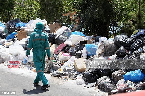 A garbage collector passes by a garbage dump in Beirut Lebanon on August 31 2015 After closing one of the main landfill sites and being stopped the...