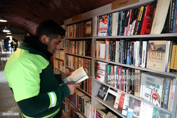 Garbage collector reads a book in a library created by the municipal employees by collecting thrown-out books at the Cankaya district of Ankara on...