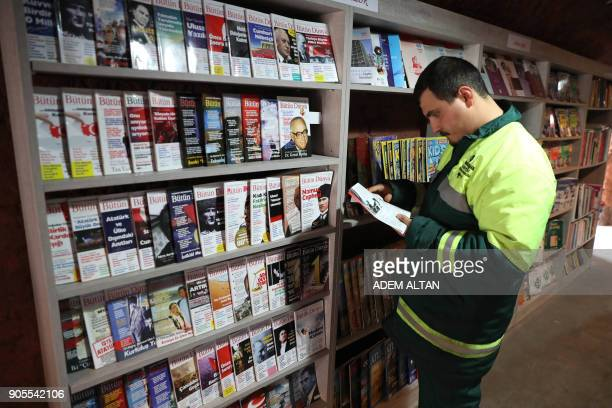 A garbage collector reads a book in a library created by the municipal employees by collecting thrownout books at the Cankaya district of Ankara on...