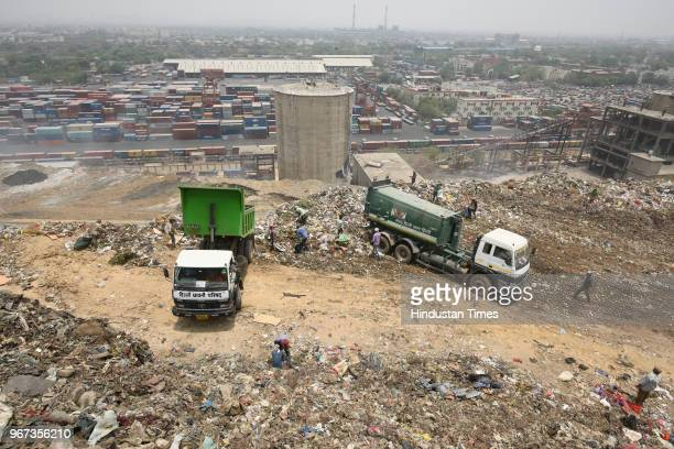 Garbage collector trucks dumps garbage at a landfill site ahead of the World Environment Day, at Okhla on June 4, 2018 in New Delhi, India. World...