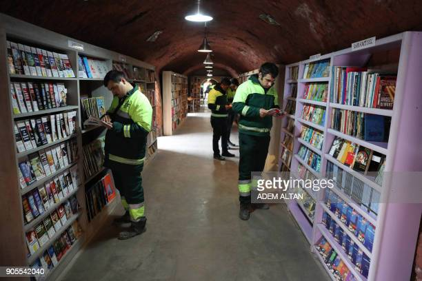 Garbage collectors look at books in a library created by the municipal employees by collecting thrown-out books at the Cankaya district of Ankara on...