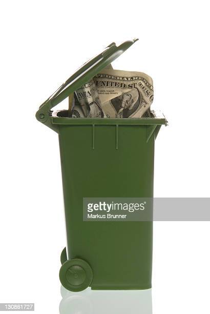 Garbage container with dollar bills, symbolic image for throwing money away, financial crisis