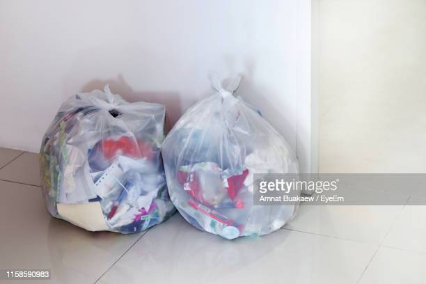 garbage in plastic bags on tiled floor at home - bin bag stock pictures, royalty-free photos & images