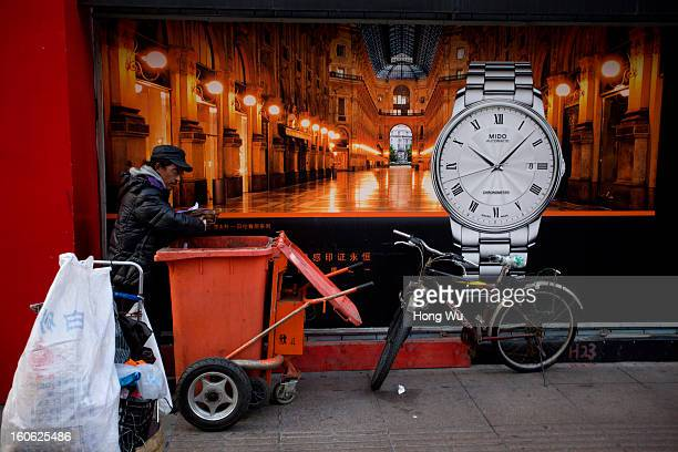 A garbage picker searches useful thing beside a clock billboard on February 3 2013 in Shanghai China