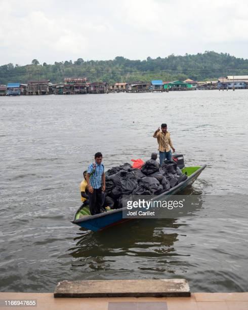 garbage pick-up boat at water village in brunei - bandar seri begawan stock pictures, royalty-free photos & images