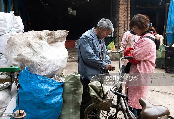 A garbage recycler gets paid from trashed materials he brought to a recycling center on April 8 2010 in Shanghai China This longtime garbage recycler...