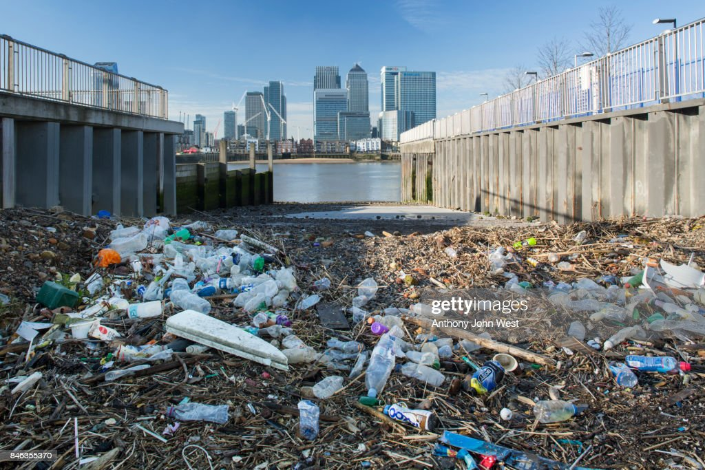 Garbage washed up by the tide opposite a skyline of International Banks, London : Stock Photo