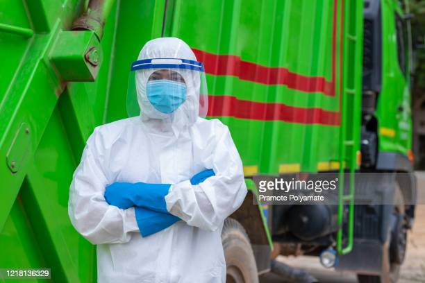 garbage workers wear ppe protective clothing. corona virus stands folded with confidence beside the garbage collection truck. - essential workers stock pictures, royalty-free photos & images