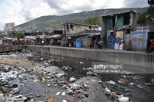 Garbages are seen in the canal of Portail Leogane in the Haitian capital PortauPrince on October 1 2016 As Hurricane Matthew threatens the Caribbean...