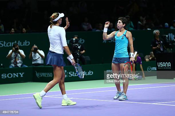 Garbine Muguruza and Carla Suarez Navarro of Spain celebrate match point against HaoChing Chan and YungJan Chan of Chinese Taipei in a doubles round...