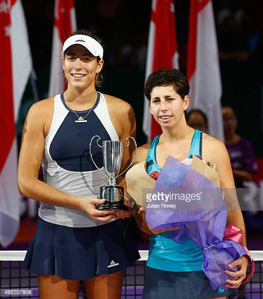 Garbine Muguruza of Spain and Carla Suarez Navarro of Spain hold up the runners up trophy after being defeated by Martina Hingis of Switzerland and...