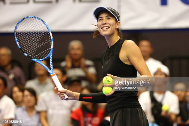 Garbine Muguruza of Spain applauds fans after her victory in her singles first round match against Belinda Bencic of Switzerland on day one of the...