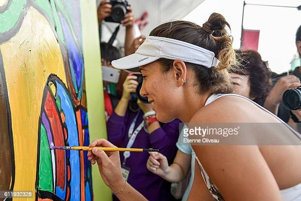 Garbine Muguruza of Spain attends the Little Painter Champion Joy Event on day two of the 2016 China Open at the China National Tennis Centre on...