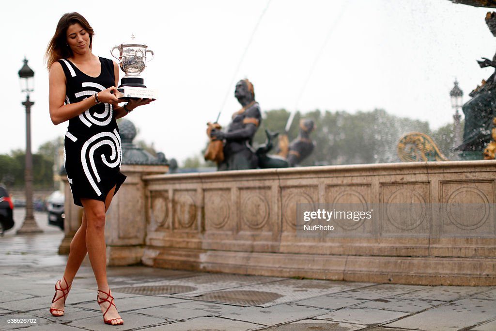 Garbine Muguruza of Spain celebrates victory and poses for the photographers with the trophy a front the fontaine at the concorde near Champs Elysees in Paris, on June 5, 2016.