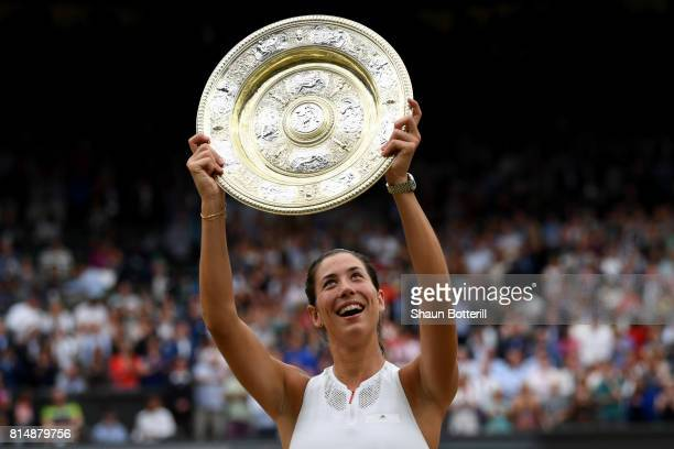 Garbine Muguruza of Spain celebrates victory with the trophy after the Ladies Singles final against Venus Williams of The United States on day twelve...
