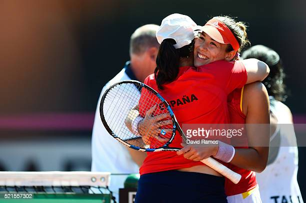 Garbine Muguruza of Spain celebrates with Spain's captain Conchita Martinez after defeating Francesca Schiavone of Italy during day one of the Fed...