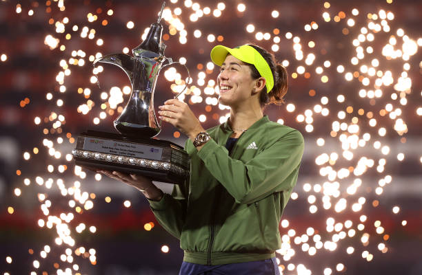 Garbine Muguruza of Spain celebrates with the trophy following victory during the Dubai Duty Free Tennis Women's Final match between Barbora...