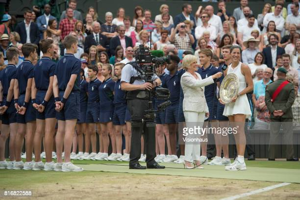 Garbine Muguruza of Spain chats to Sue Barker of the BBC after victory in the Ladies Singles final against Venus Williams of The United States on day...
