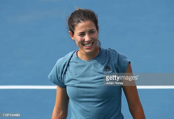Garbine Muguruza of Spain enjoys her time playing football and tennis with World Cup winner Carles Puyol of Spain during day three of the Miami Open...