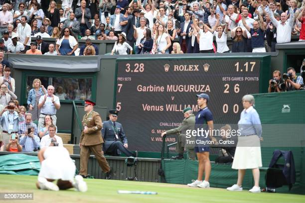 Garbine Muguruza of Spain falls to her knees as the video replay confirms her victory in the Ladies Singles final as coach Conchita Martinez and...