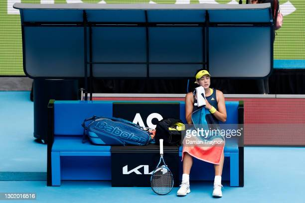 Garbine Muguruza of Spain looks on as she sits down in between games in her Women's Singles fourth round match against Naomi Osaka of Japan during...