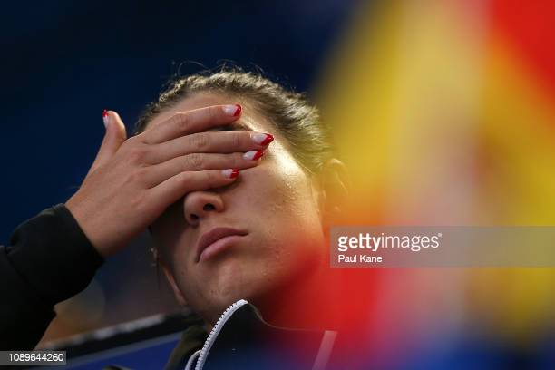 Garbine Muguruza of Spain looks on from the team box injured while watching the mixed doubles match between David Ferrer of Spain partnered with...