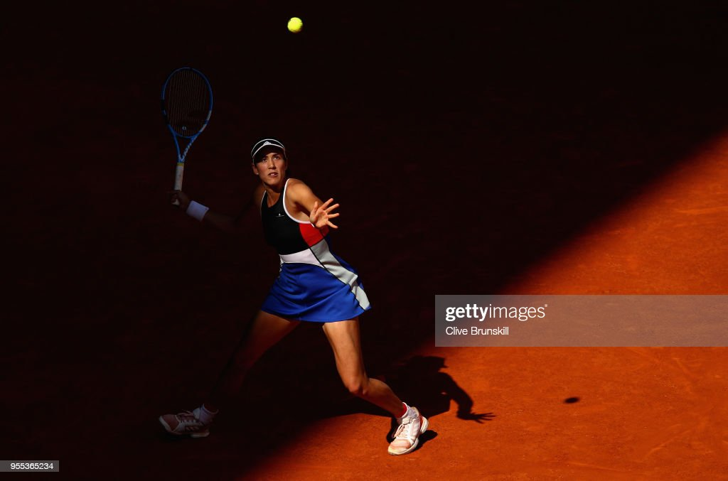 Garbine Muguruza of Spain looks up at a high ball as she gets ready to play a forehand against Shuai Peng of China in their first round match during day two of the Mutua Madrid Open tennis tournament at the Caja Magica on May 6, 2018 in Madrid, Spain.