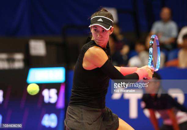 Garbine Muguruza of Spain plays a backhand during her singles first round match against Belinda Bencic of Switzerland on day one of the Toray Pan...