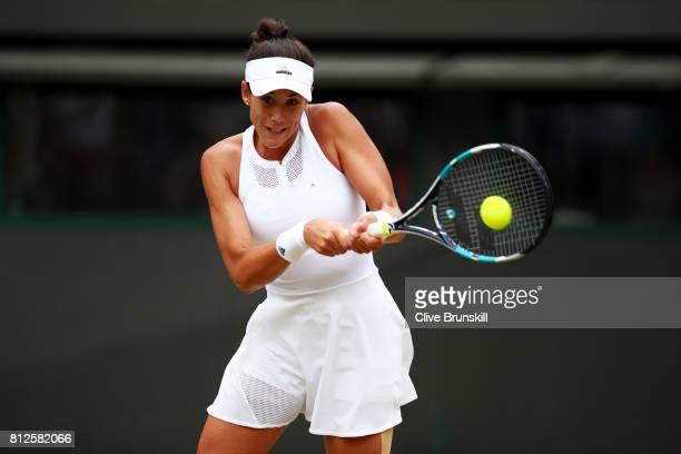 Garbine Muguruza of Spain plays a backhand during the Ladies Singles quarter final match against Svetlana Kuznetsova of Russia on day eight of the...