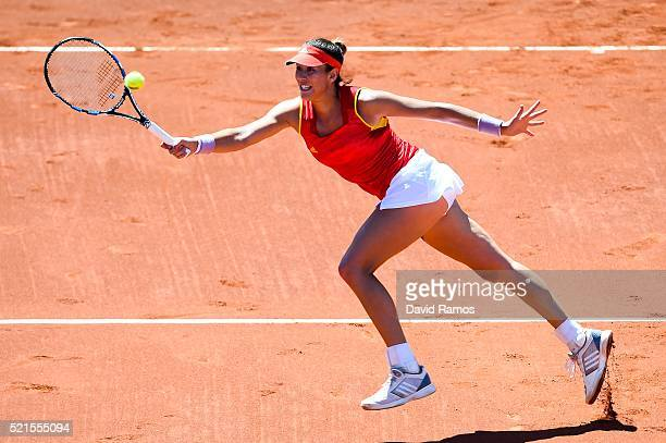 Garbine Muguruza of Spain plays a forehand against Francesca Schiavone of Italy during day one of the Fed Cup World Group Playoff Round match between...