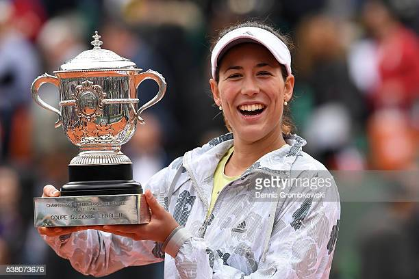 Garbine Muguruza of Spain pose with the trophy following her victory during the Ladies Singles final match against Serena Williams of the United...