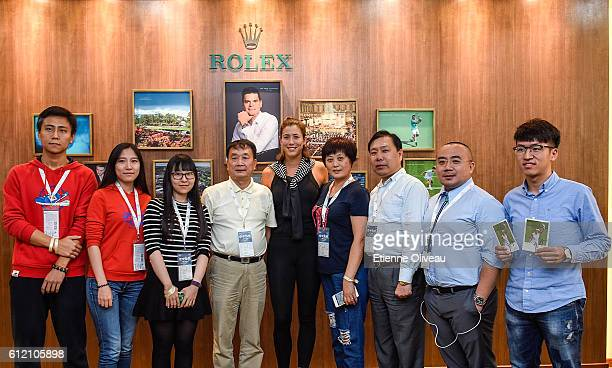 Garbine Muguruza of Spain poses for a photograph with staff at the Rolex Skybox on day three of the 2016 China Open at the National Tennis Centre on...