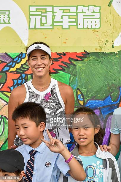 Garbine Muguruza of Spain poses with kids during the Little Painter Champion Joy Event on day two of the 2016 China Open at the China National Tennis...