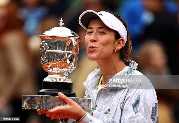 Garbine Muguruza of Spain poses with the trophy following her victory during the Ladies Singles final match against Serena Williams of the United...