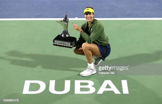Garbine Muguruza of Spain poses with the trophy following victory during the Dubai Duty Free Tennis Women's Final match between Barbora Krejcikova...