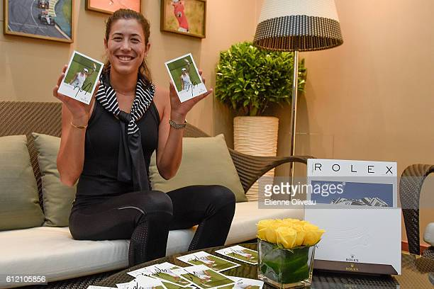 Garbine Muguruza of Spain signs autographs at the Rolex Skybox on day three of the 2016 China Open at the National Tennis Centre on October 3 2016 in...