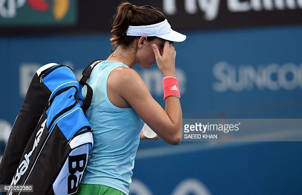 Garbine Muguruza of Spain walks off follwoing her retirement from the game against Alize Cornet of France in their women's single semifinal match at...