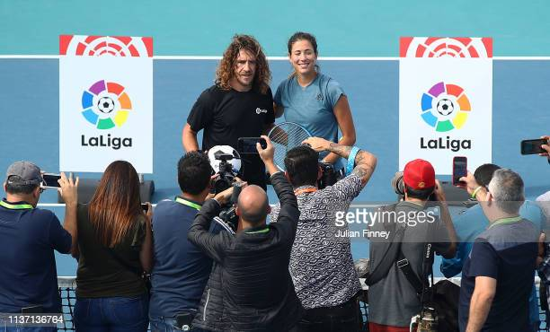 Garbine Muguruza of Spain with World Cup winner Carles Puyol of Spain during day three of the Miami Open tennis on March 20 2019 in Miami Gardens...