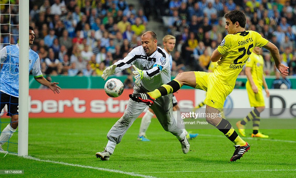 Garbor Kiraly (C) of Muenchen challenges Sokratis of Dortmund during the DFB Cup match between TSV 1860 Muenchen and Borussia Dortmund at Allianz Arena on September 24, 2013 in Munich, Germany.