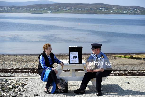 Garda Alan Gallagher and Presiding Officer Carmel McBride carry the polling box for the referendum on abortion law a day early for the few people...