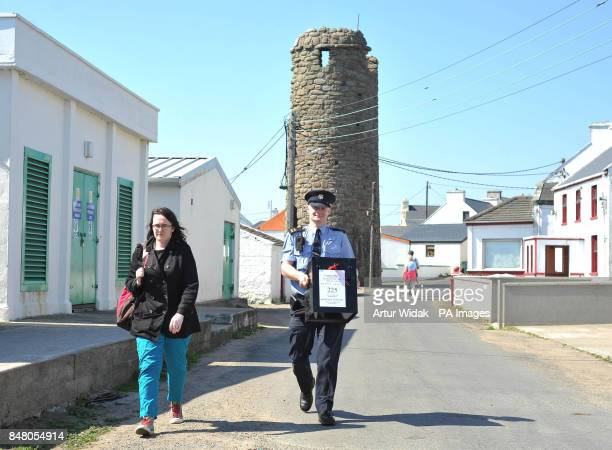 Garda Eugene Organ and Polling officer Clar Ni Shearcaigh carry a ballot box to the polling station on Tory Island off the coast of Donegal Ireland...