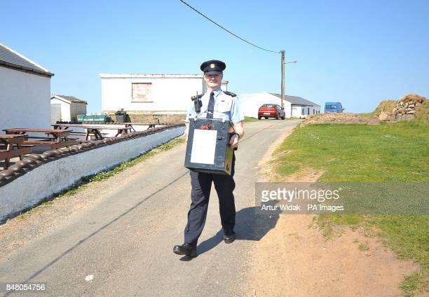 Garda Eugene Organ carrying a ballot box to the polling station for voting on the fiscal treaty referendum on Tory Island off the coast of Donegal...