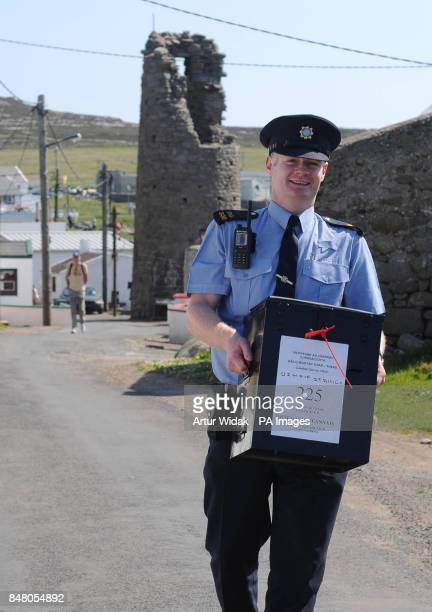 Garda Eugene Organ leaves the polling station with the ballot box after voting on the fiscal treaty referendum on Tory Island off the coast of...