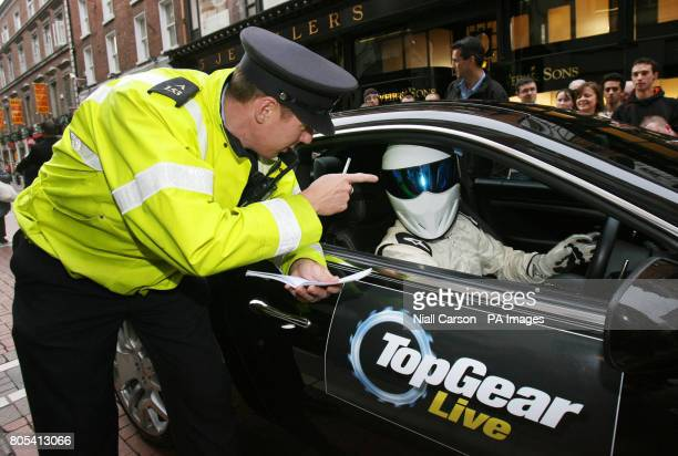 Garda Hugh Shovlin helps to promote the Top Gear Live tour 2009 by giving The Stig a speeding ticket as he arrived in Dublin the tour runs from...