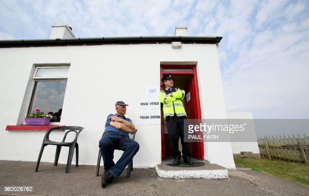 TOPSHOT Garda officer Pat McElroy chats with Jimmy Sweeney whose home has become a temporary Polling Station on Gola Island off the Donegal coast...