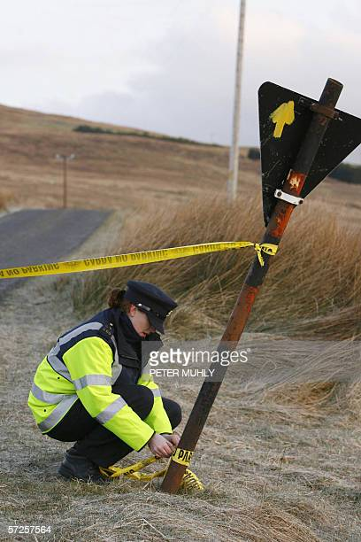 Garda officer places tape along a road leading to the remote house in Donegal Ireland of Denis Donaldson 05 April 2006 Donaldson a former British...